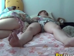 Asian teens dowsing bed